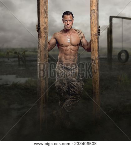 Shirtless Soldier With Wooden Timber In A Swampland.