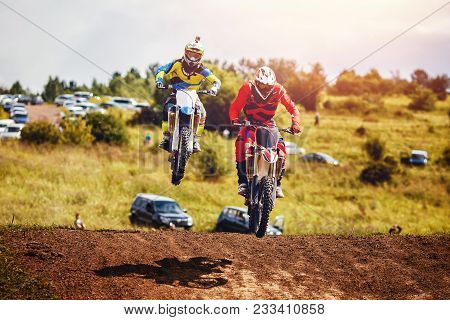 Racer On Dirtbike Motorcycle Jumps And Takes Off Over The Track, In Background The Opponent Is Catch