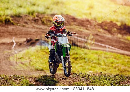 Racer Child On Motorcycle Participates In Motocross Cross-country In Flight, Jumps And Takes Off On