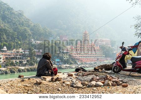Poor Man Sits On The Banks Of The Ganges River And Looks Towards The Temple Tera Manzil Temple. Morn