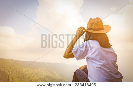 Young Traveling Woman Wearing Hat And Sitting On The Top Of The Mountain Cliff With Relaxing Mood An