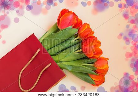 Fresh Orange Tulip Flowers  In Paper Bag On Beige Background. Top View With Copy Space.