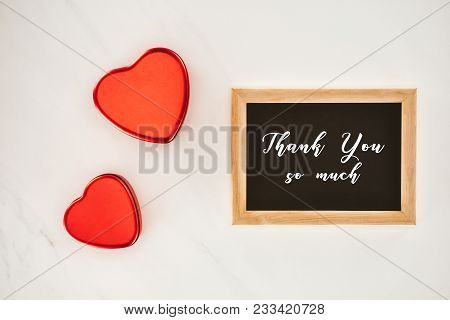 Top View Of Blackboard In Frame With Thank You So Much Lettering With Heart Shaped Isolated On White