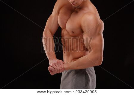 A Sexy Body-builder On A Black Background. Dramatic Portrait Of An Athlete. Drying. Relief And Sculp