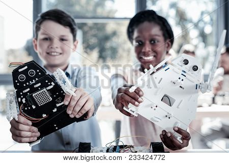 Check These Out. Selective Focus On Monochrome Robotic Machines Held By Smiling Youngsters Standing
