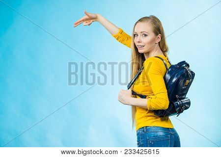 Happy Young Blonde Teenage Girl Going To School Or College Wearing Backpack Pointing With Finger At