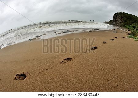 Lonely Footprints Along Shore Of Stormy Ocean, Fisheye Seascape With Footprints On The Shore
