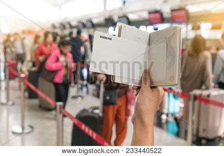 Close Up Of Young Woman Holding Blank Boarding Pass And Passport At Airport Counters Reception Area