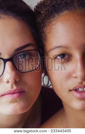 Portraits of two happy girls best friends with half faces cheek to cheek
