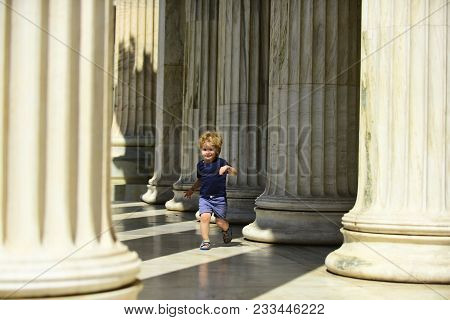 Cute Child Boy Running Between Columns Of Ancient Building In Greek Style. Kid Walks On Sunny Day, B