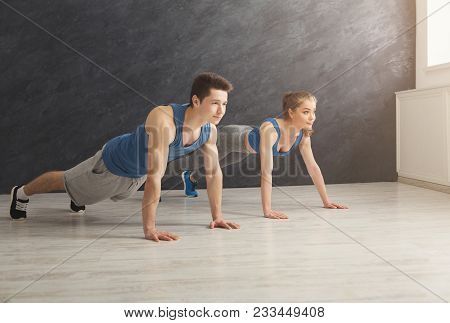 Young Man And Woman Workout In Fitness Club. Fitness Couple Making Plank Or Push Ups Exercise, Train