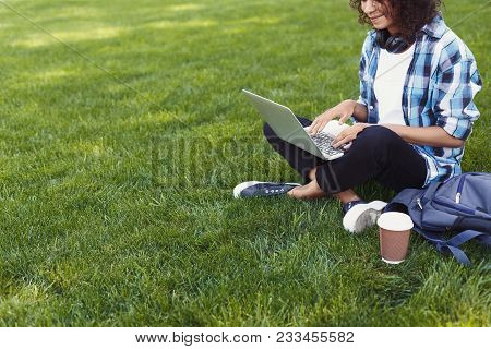 Unrecognizable Smiling Black Woman Sitting Outdoors On Grass With Laptop, Typing, Surfing Internet,