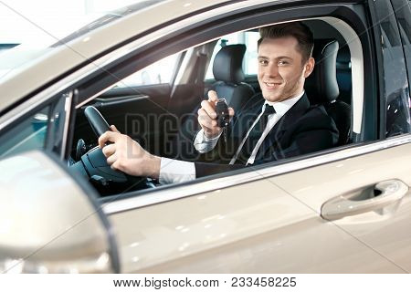 Formal Wearing Young Man Behind The Wheel. He Is Looking At Camera, Showing The Car Key And Smiling.