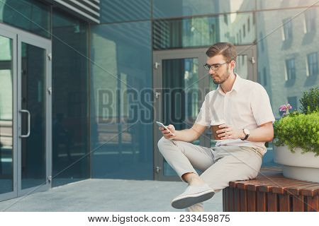 Thoughtful Young Man Texting On Phone And Drinking Coffee While Sitting On Bench Near A Modern Offic