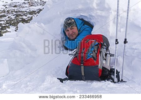 Smiling Happy Hiker Peeking Out Of A Small Snowy Hut Igloo In Winter Next To A Lying Backpack