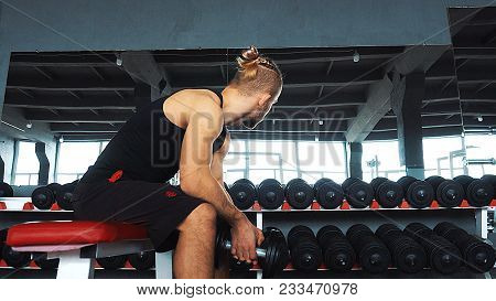 A Young Man Sitting On A Bench In The Gym After His Workout And Looking Down. A Young Athlete Is Res