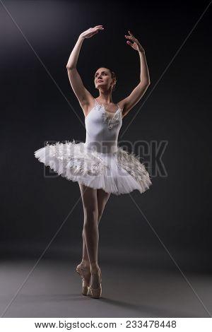 Ballerina In Tutu And Pointe Dancing Gracefully In Dark Room