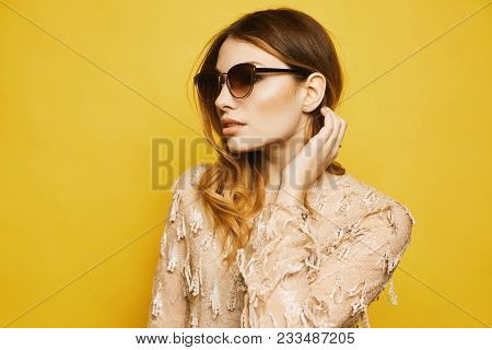Beautiful And Fashionable Model Girl, In Beige Dress And Sunglasses, Posing At Yellow Background.