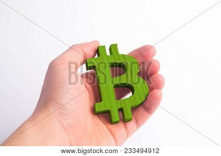 Hand Holds A Wooden Bitcoin On A White. Crypto Currency, Blocking Technology. The Collapse And Rise