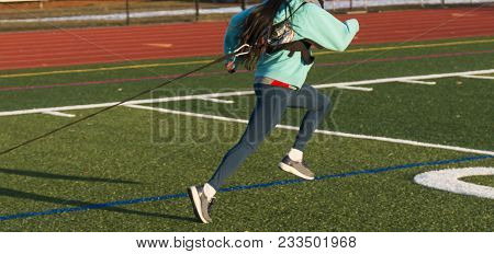 A High School Girls Pulls A Weighted Sled On A Green Turf Field During Track And Field Speed Practic