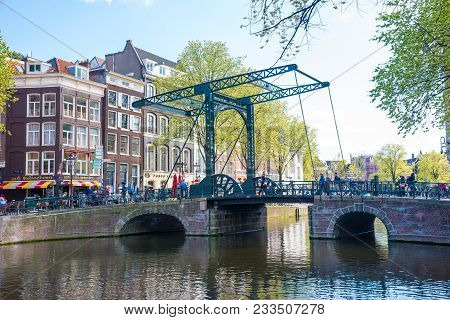 Amsterdam, Netherlands - April 19, 2017: Beautiful View Of Amsterdam Canals With Bridge And Typical