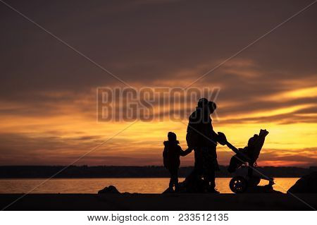 Young Family With Children And A Baby In A Pushchair Silhouetted Against An Vivid Orange Ocean Sunse