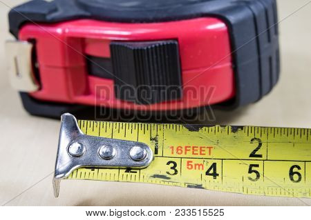 Measuring Tools In A Carpentry Workshop. Steel Measuring Tape On A Wooden Table.