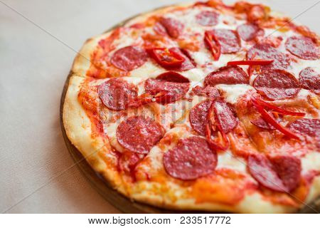 Spicy Pizza With Cheese And Pepperoni. Pepperoni Pizza On Table.