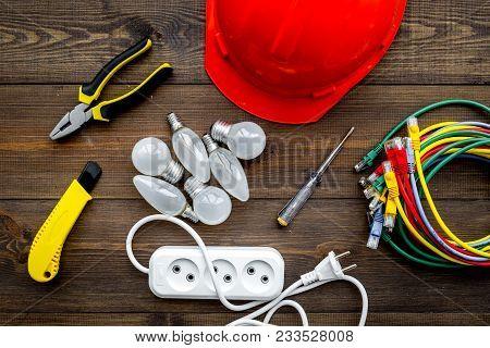 Electrician Work Concept. Hard Hat, Tools, Cabel, Bulb, Socket Outlet On Dark Wooden Background Top