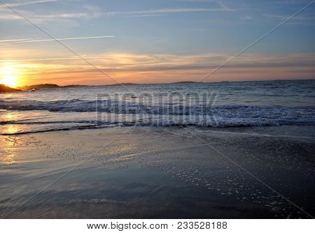 Sunset On A Calm Beach In Massachusetts With Small Waves.