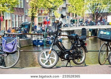 Amsterdam, Netherlands - April 20, 2017: Electric Bike On The Bridge In Amsterdam. Canals Of Amsterd