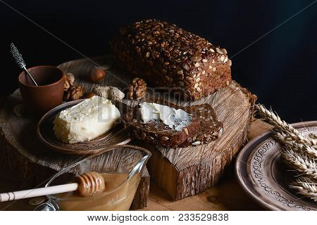 Black Sliced Bread On The Board, Butter And Honey, Flax Seed, Than Slicing Bread On The Table And A