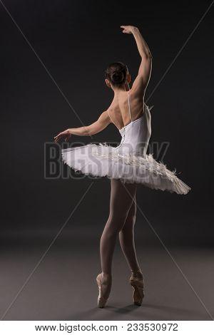 Ballerina In Tutu And Pointe Dancing Gracefully In Dark Room Rearview