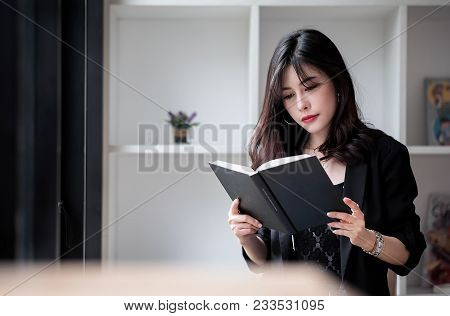 Beautiful Woman In Black Suit Sitting And Reading A Book In White Room