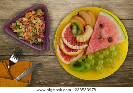 Sliced Fruit On A Wooden Background. Sliced Fruit On A Plate