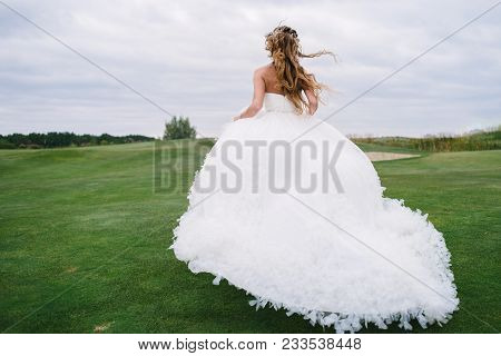 Full length body portrait of beautiful bride in fashion white wedding dress with feathers running away through green golf course, back view. Runaway bride poster