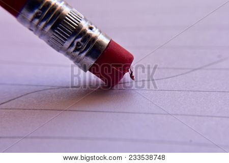 Close Up Of A Wooden Pencil With Red Eraser Laying On A Sheet Of White Paper With Blue Lines On It.