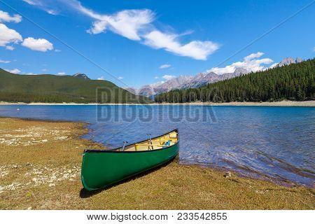 Green Canoe On The Shore Of A Mountain Lake, Peter Lougheed Provincial Park, Alberta