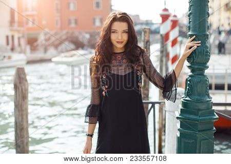 Attractive Young Romantic Woman Standing On The Pier Against Beautiful View On Venetian Chanal With