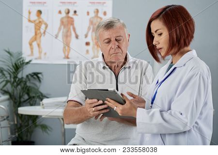 Female General Practitioner Showing Analysis Results On Tablet Computer To Senior Patient