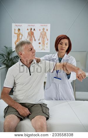 Senior Man Attending Rehabilitation Theraphy In Local Hospital
