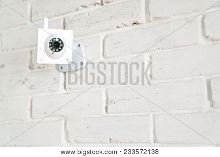 White Web Surveillance Camera On A White Brick Wall. Technologies Of Video Surveillance And Security