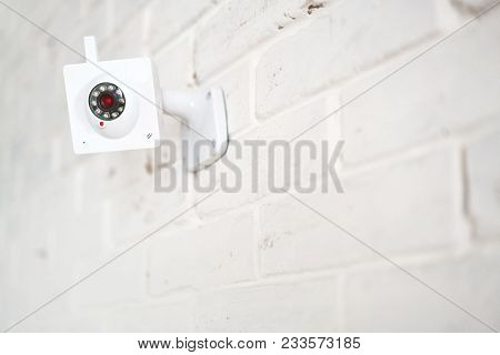 White Web Surveillance Camera On A White Brick Wall. Security Technologies.