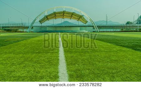 White Outdoor Covered Stage On Fifty Yard Line Of Sports Field With Lush Green Artificial Grass And