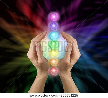 Sending The Seven Chakras Vortex Healing Energy - Female Parallel Hands Against A Multicoloured Back