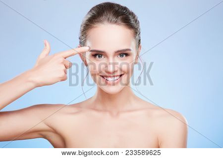 Woman Pointing At Temple And Smiling