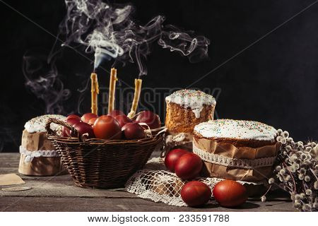 Traditional Painted Chicken Eggs, Candles With Smoke And Easter Cakes With Catkins On Table