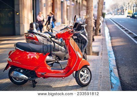 Barcelona, Spain - February, 09, 2018. Red Vespa Scooter On The Street Of Barcelona, Spain.