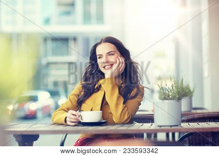 drinks and people concept - happy young woman or teenage girl with cup drinking cocoa at city street cafe terrace and dreaming