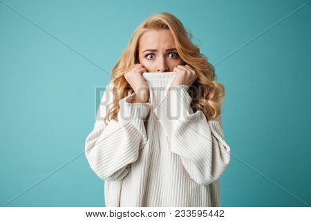 Portrait of an astonished young blonde woman in sweater covering mouth with hands isolated over blue background